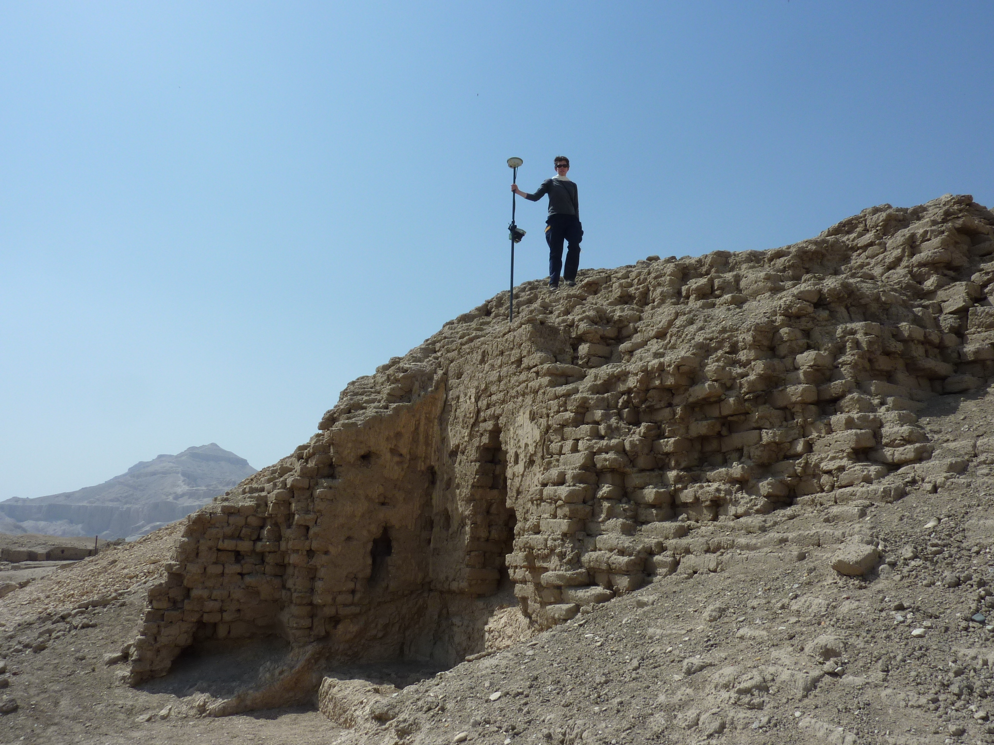 Author standing on a mudbrick pyramid with a differential GPS de