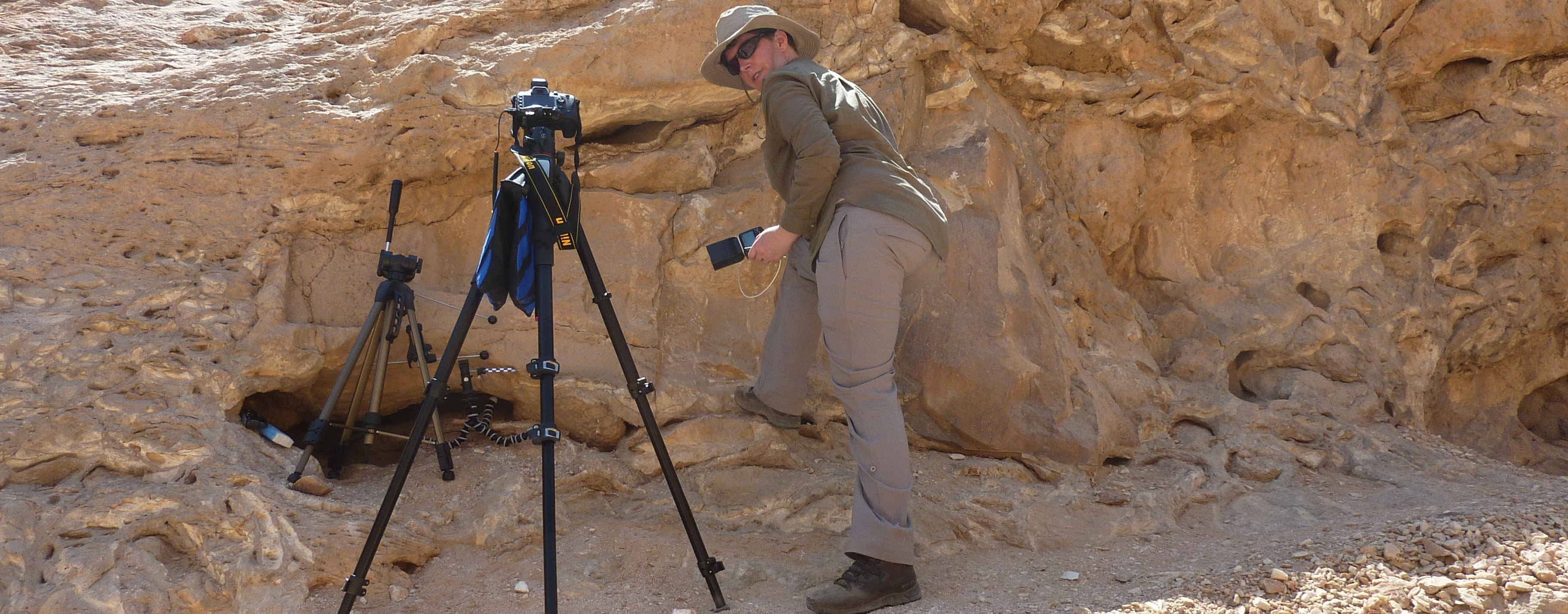 Author and tripods set up against an ancient inscription on a rock face.