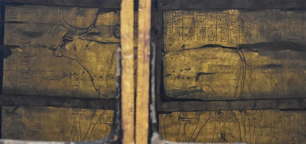Image shows the rear interior wall of a golden shrine, with a large cow held up by various gods, with hieroglyphs above, seen past the vertical uprights of the shrine doors. The