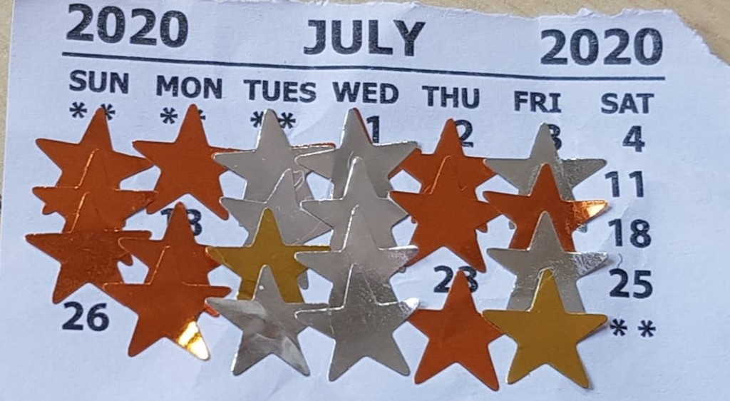 A calendar from July 2020 with bronze, silver and gold stars overlying the dates.